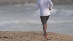 A young man runner getting a workout running in the sand on the beach , slow mo Stock Footage
