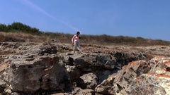 Lady model walking on the edge of sea cliffs kaliakra yaylata bulgaria Stock Footage