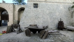 An antique wagon and an old wooden medieval pillory. Walls of the medieval city Stock Footage