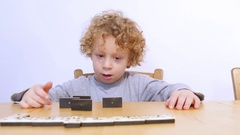 Little blond boy playing with dominoes Stock Footage