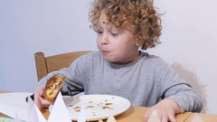 Little blond boy eating a king cake Stock Footage