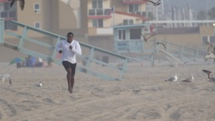 A young man barefoot running on the beach , slow motion. Stock Footage