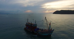 Aerial: Lonely fishing boat in the sea at sunset. Stock Footage