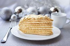 Piece of layer cake with custard and walnuts on a plate with Christmas ball.. Stock Photos