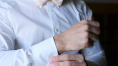Man buttons up sleeves of white shirt Stock Footage