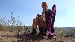 Young blonde woman tourist wrapped in a vinous blanket sitting on camping c.. Stock Footage