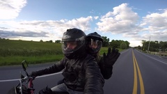 Motorcycle selfie as passenger waves to camera Stock Footage