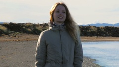 Medium shot of young tourist is walking on black volcanic beach in Reykjavik Stock Footage