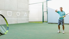 Instructor or coach teaching child how to play tennis use the wall for training Stock Footage