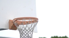 Basketball going into outdoor basketball hoop. Stock Footage
