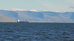 Trawler in Atlantic ocean near coast of Reykjavik, snow on the top of mountain Stock Footage