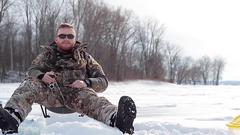 Ice fishing man wearing camo slider view Stock Footage
