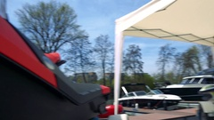 Parked boat, one in a cart under a white tent in the foreground, trees and the Stock Footage