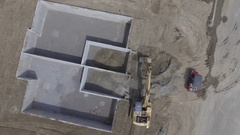 Aerial high hoe shovel drops sand into foundation 4k Stock Footage
