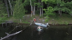 Aerial guy runs into water to swim at camping site 4k Stock Footage