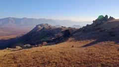 Beautiful rocky mountain aerial grass horizon skyline valley sunny blue sky Stock Footage