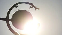 Single hit to the gong and swinging silhouette against sun Stock Footage