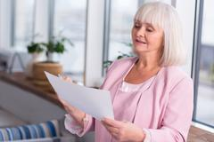 Friendly elderly lady consulting a source Stock Photos
