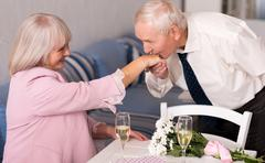 Attentive elderly man kissing his womans hand Stock Photos