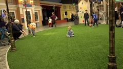 Children and kids playing on green artificial grass in the Childrens World Stock Footage