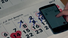 Female hand compare smart phone and paper calendars Stock Footage