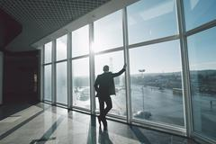 Time to think. Business man alone in room with panoramic windows. Stock Photos