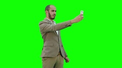 Young businessman taking selfies on phone on a Green Screen, Chroma Key Stock Footage