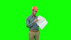 Young engineer in helmet checking construction plan on a Green Screen, Chroma Stock Footage