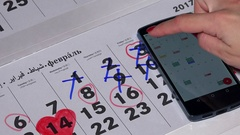Female hand compare smart phone android calendar with paper calendar Stock Footage