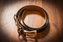 Leather Belt Men Dress Rolled Up on Wooden Floor Vignette Spotlight Floor Stock Photos