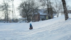 Children are rolling snowy downhill on sleds Stock Footage