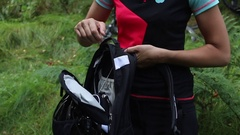 Woman closing her mountainbike backpack with bike in the background Stock Footage