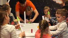Children in the classroom working with a multi-colored paper and glue Stock Footage