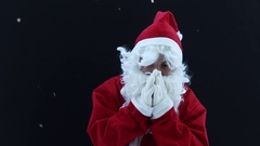 Santa Claus shivering and warm up with hands in front of black background Stock Footage