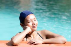 Dreamy woman in a bathing cap relaxes in a swimming pool Stock Photos