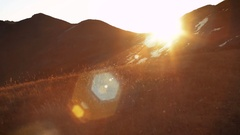 Sun rising from behind snow mountains. Tight shot with a beautiful lens flare Stock Footage