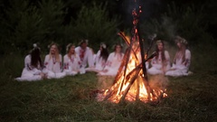 Midsummer. Young people in Slavic clothes sitting in the woods near the fire Stock Footage