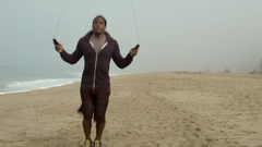 A young man working out and jump roping on the beach. Stock Footage