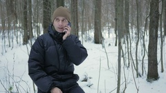 Young man sitting in the winter forest and talking on the phone. He admires the Stock Footage
