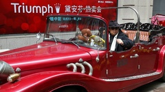 Chinese young man posing as a mafia god father boss in a car in Shanghai, China Stock Footage