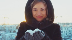 Close-up portrait young adult woman blowing snowflakes outdoors Stock Footage