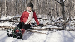 Woman relaxes and sits in forest wearing snowshoes in winter Stock Footage