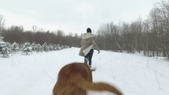 Woman and her big dog running playfully in deep snow 4k Stock Footage