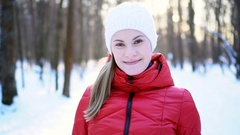 Beautiful young woman running in winter park, inviting to join, smiling, having Stock Footage