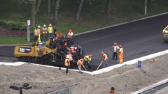 Asphalt paver and road workers paving hot asphalt Stock Footage