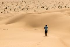 Man tourist desert rub al khali Oman running in sand Stock Photos