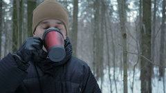 A young man drinking a hot beverage from a thermos in a winter forest. The man Stock Footage