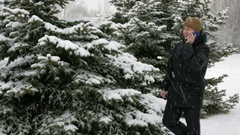 A young man goes on a winter forest and talking on the phone. Big snowfall. He Stock Footage