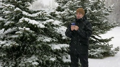 Young man typing a sms message on the phone in the winter snowy forest. Big Stock Footage