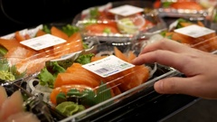 Woman buying salmon sashmi inside Price Smart foods store Stock Footage